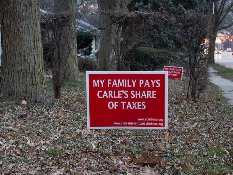 A sign in front of a home on Lincoln Avenue in Urbana protests Carle Hospital's tax-exempt status.