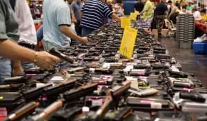 Attendees examining guns for sale at a gun show in Houston, Texas.