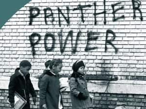 "African American school children walk past spray painted sign which reads, ""Panther Power"""