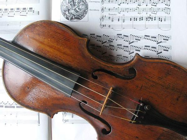 violin laying on top of a sheet of music