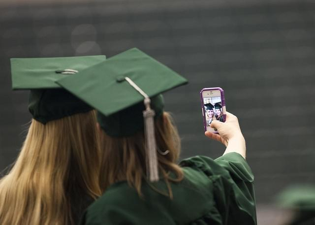 Two new college graduates in caps and gowns capture the moment by taking a selfie.