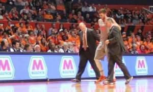 Illinois forward Michael Finke is helped off the court after hurting his knee in a collision with another player.