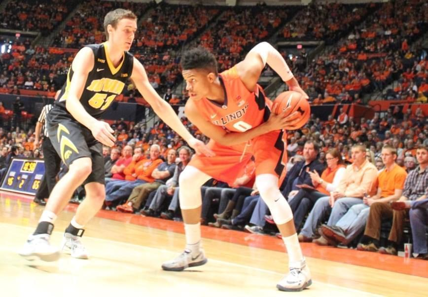 Illini player D.J. Williams shields the ball from Iowa defender Nicholas Baer.