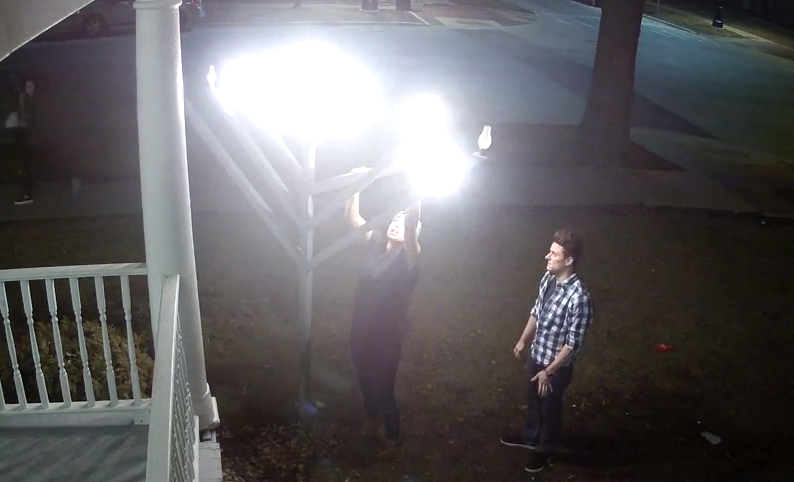 Screenshot of security video shows Ruby Fernandez-Rivera vandalizing the outdoor menorah at the Illini Chabad Center for Jewish Life, while a second person watches.