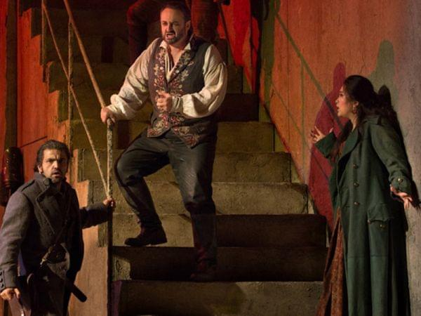 three cast members performing on stairs on the stage