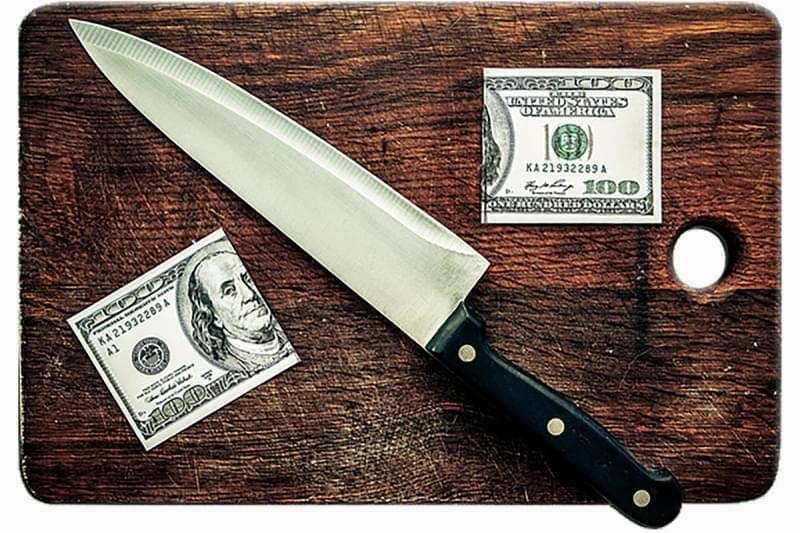 A dollar being cut in half with a knife on a cutting board.