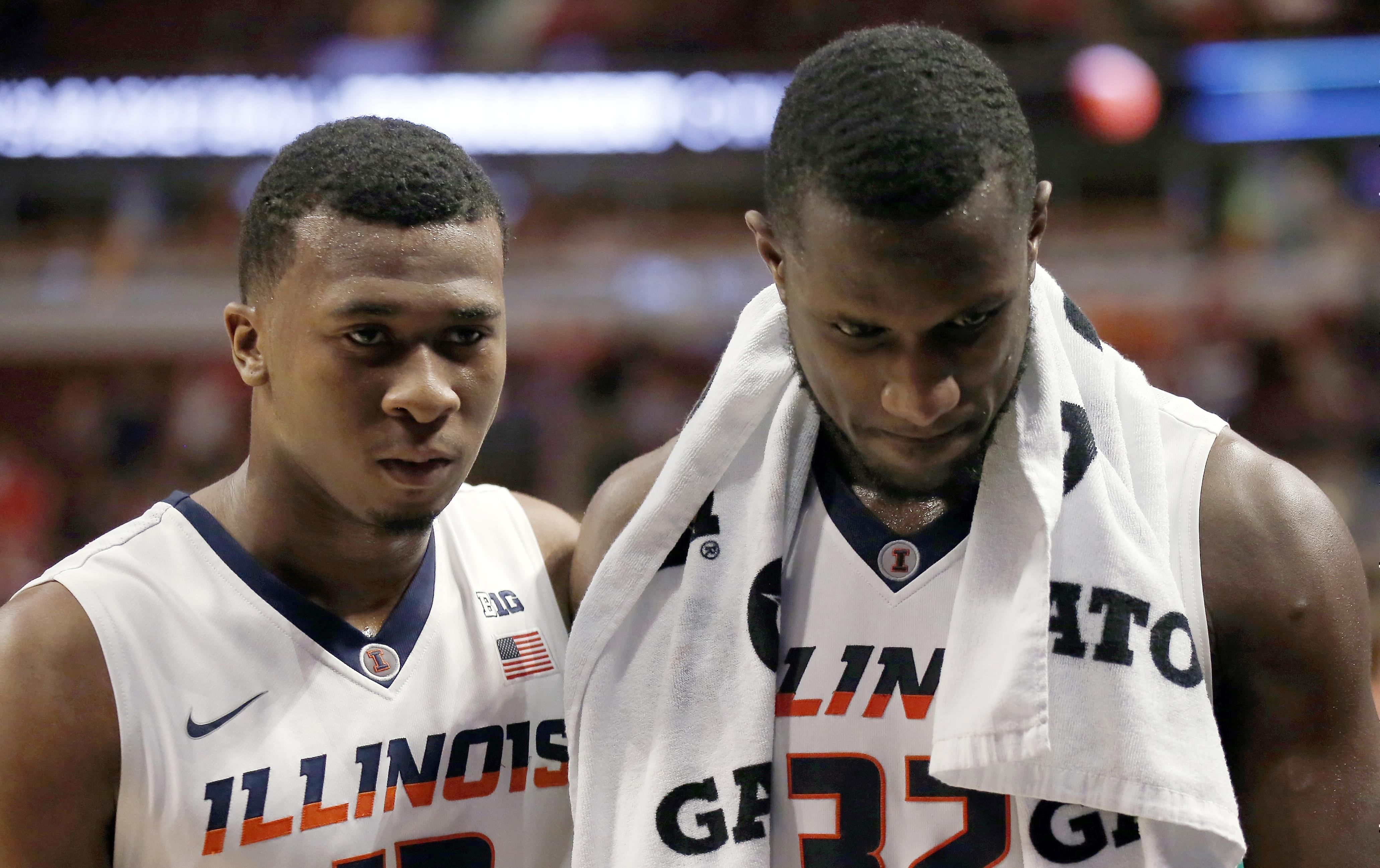 Illinois' Leron Black (12) and Nnanna Egwu (32) walk off the court after an NCAA college basketball game against Michigan in the second round of the Big Ten Conference tournament, Thursday, March 12, 2015, in Chicago.