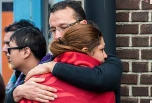 People comfort each other after being evacuated from Brussels airport, after explosions rocked the facility in Brussels, Belgium, Tuesday March 22, 2016.