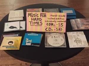 Compact discs, etc. spread out on a table for sale.