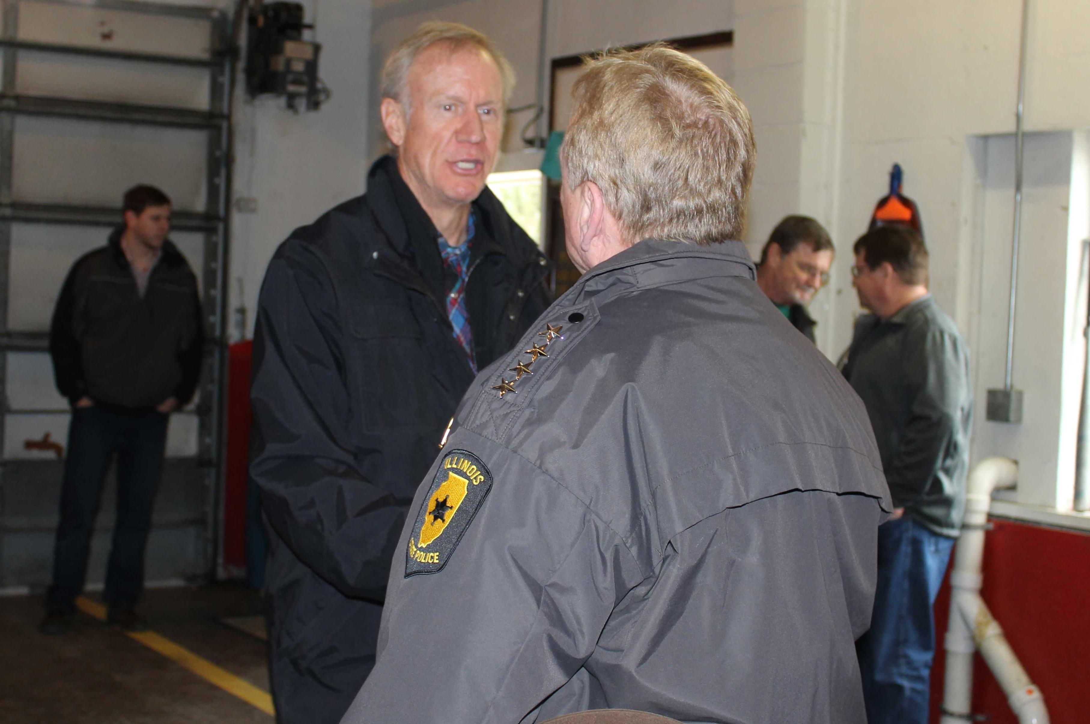 Gov. Bruce Rauner meets with other state and local officials when surveying flood damage in Villa Grove January 3.