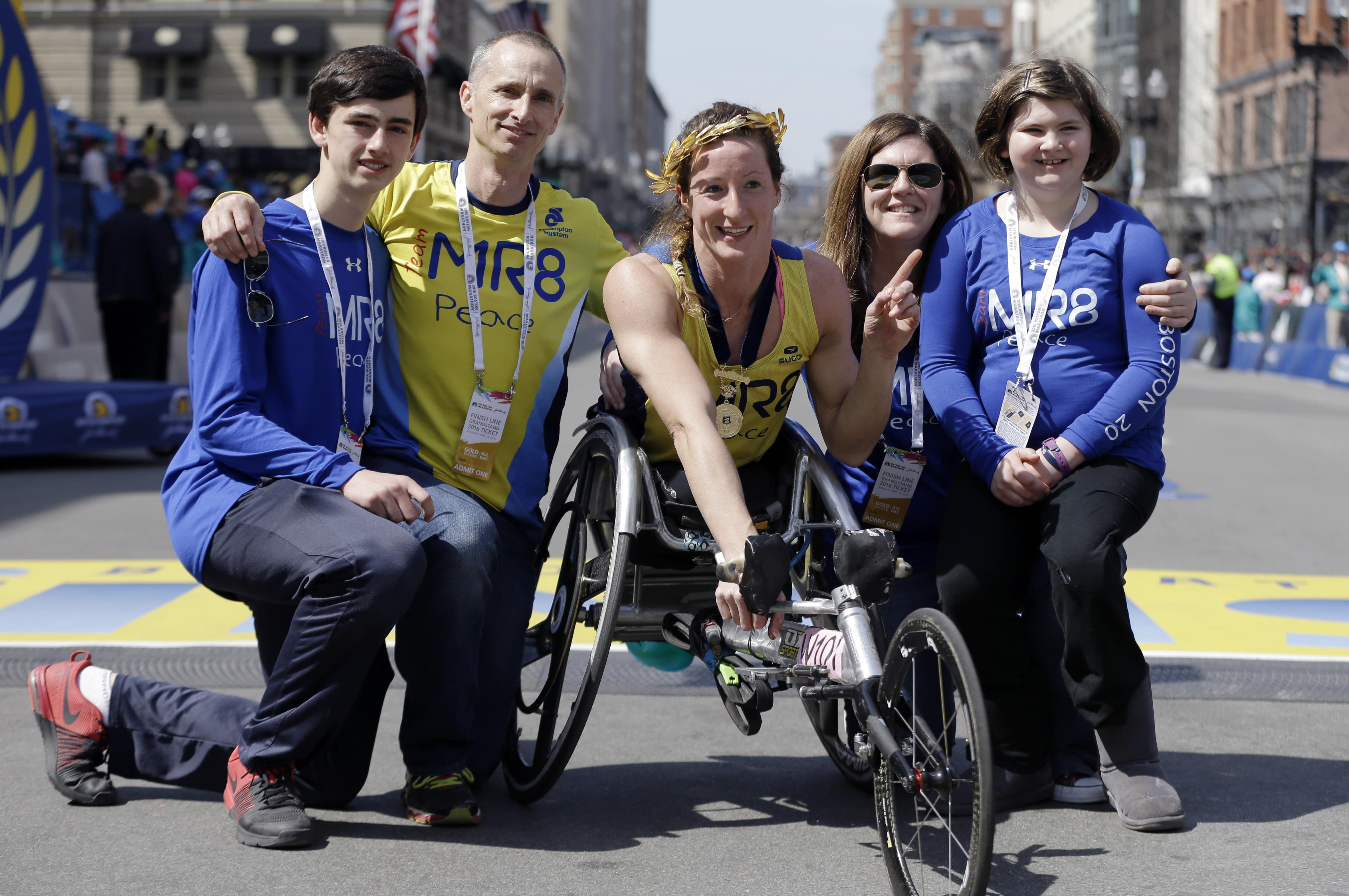 Tatyana McFadden, of Clarksville, Md., center, winner of the women's wheelchair division of the 120th Boston Marathon, poses with the family of 2013 bombing victim Martin Richard, on Monday, April 18, 2016, in Boston. From left Henry and Bill Ri