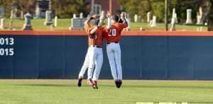Three Illini baseball players jumping together in celebration after a win.