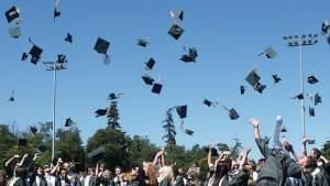 At a college graduation ceremony, new graduates throw their caps into the air.