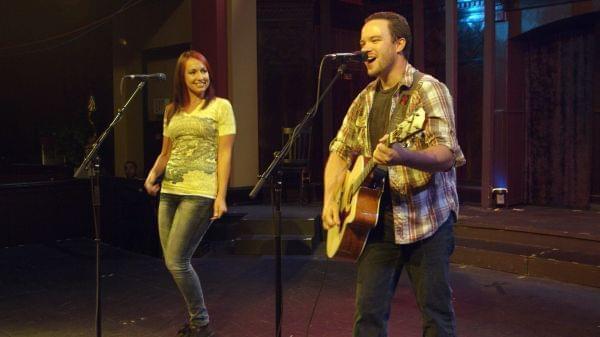 A woman sings while a man plays a guitar.