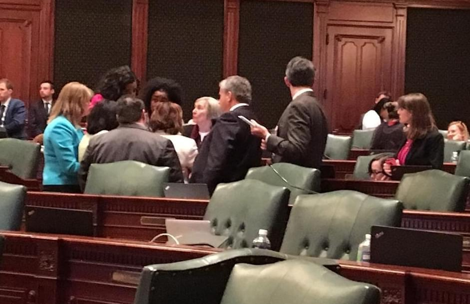 Democratic House members huddle around Majority Leader Barbara Flynn Currie's desk.