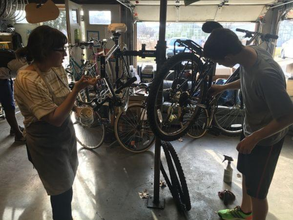 Two students stand working on bikes held up on workstands.