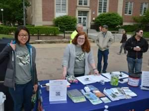 A plaza outdoors where two smiling people facing camera stand behind a table covered with brochures, etc., with other people standing around behind