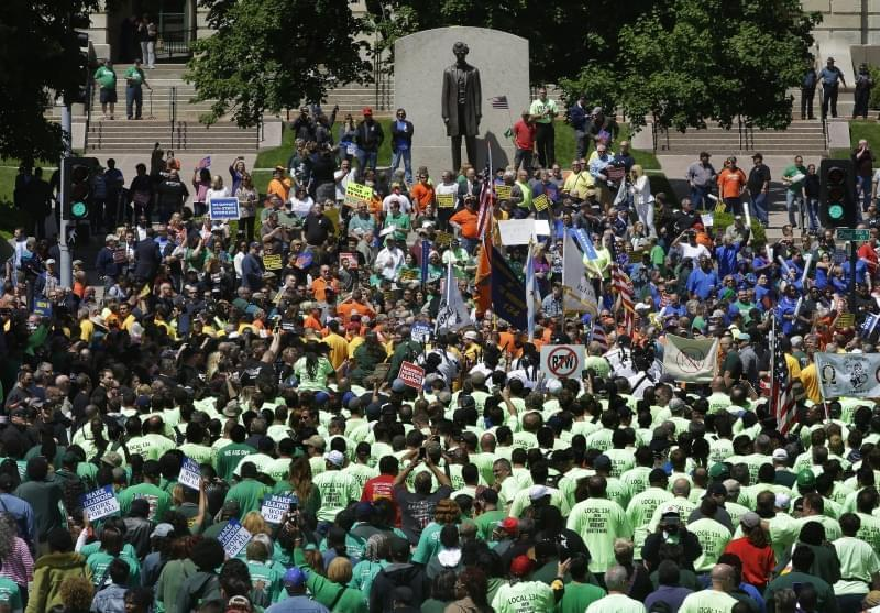 Union supporters rally against Republican Illinois Gov. Bruce Rauner's calls to change collective bargaining policies, in front of the Illinois State Capitol Wednesday, May 18, 2016, in Springfield, Ill. The march is organized by a coalition of