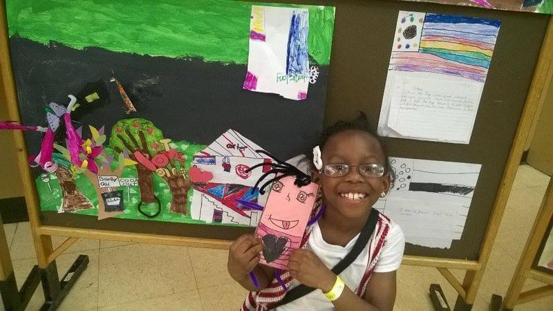 third grader Alannah Lowery shows some of the artwork she created as part of the 21st Century program