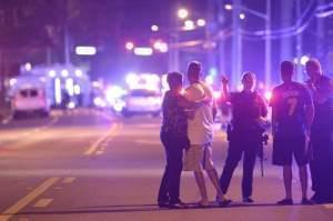Orlando police officers direct family members away from a shooting at a nightclub in Orlando, Fla., on Sunday.