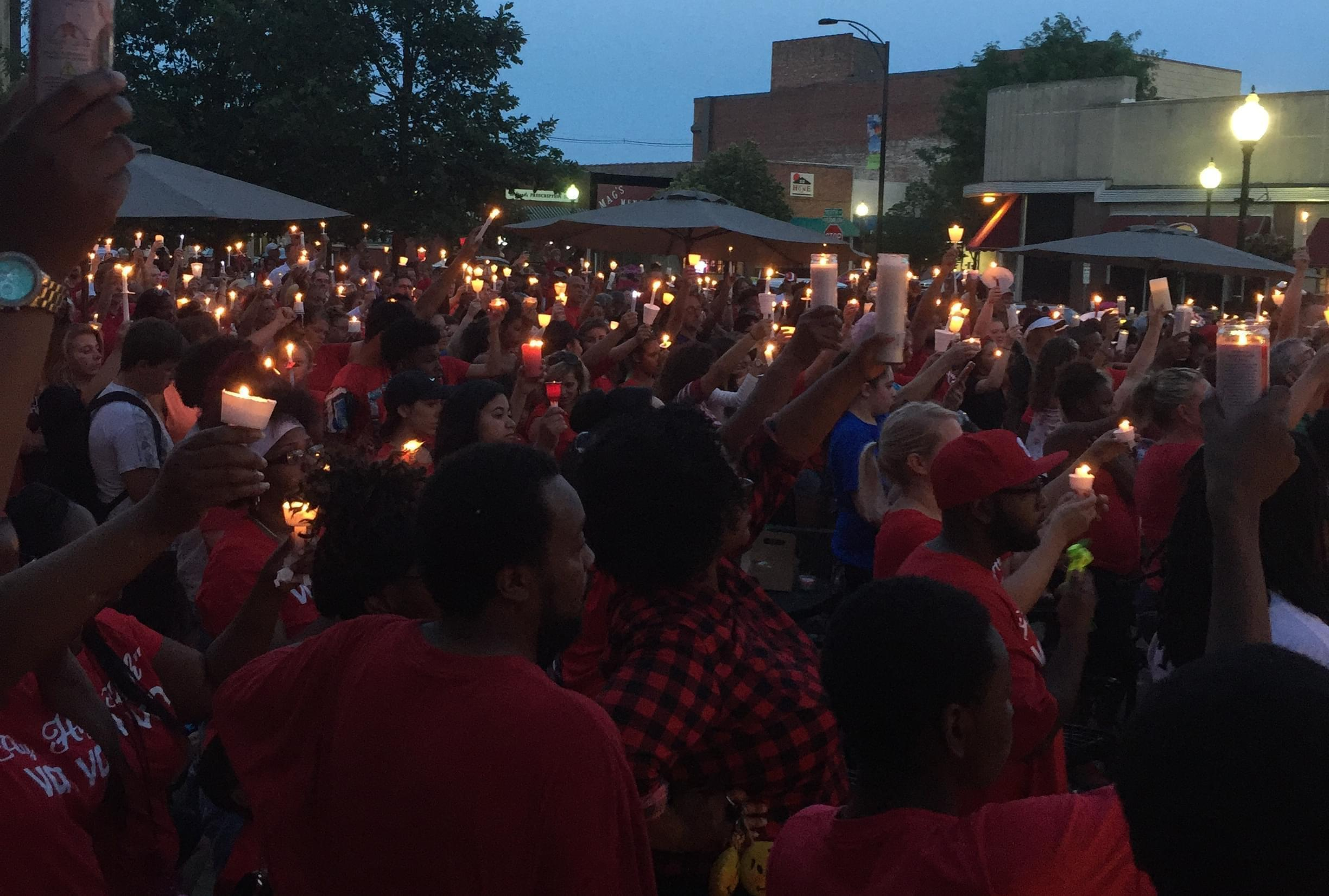 Hundreds of people raise up lit candles at a memorial vigil for Devon McClyde.