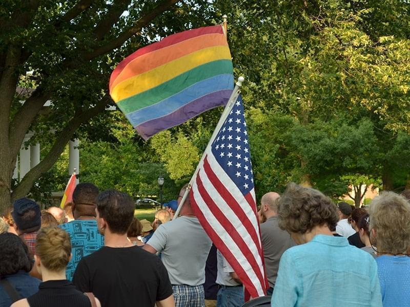 Two people hold an American flag and a LGBTQ Pride Flag at a Champaign, IL, Vigil for Orlando