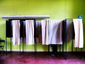 A row of voting booths, with only one of them occupied.