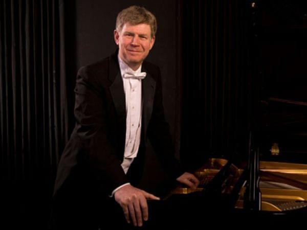 Ian Hobson standing next to a piano