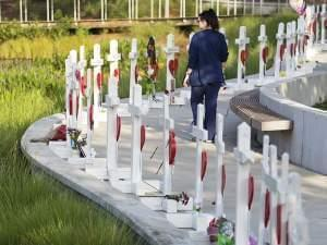 Woman walking past installation of white crosses in Orlando, Florida
