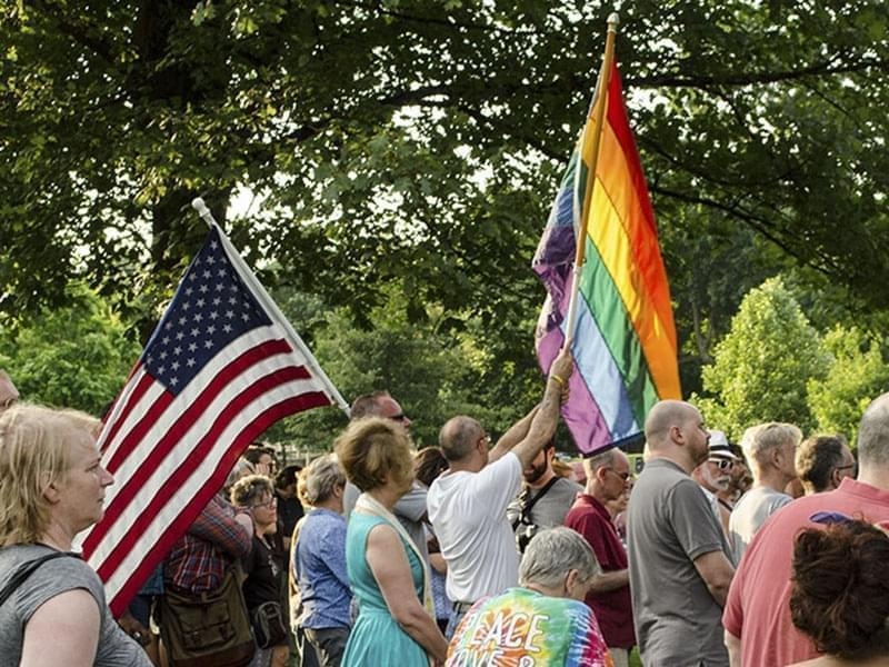 Men holding an American Flag and a Rainbow Pride flag together