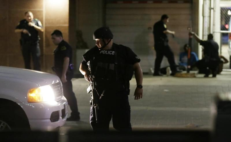 Dallas police detain a driver after several police officers were shot in downtown Dallas, Thursday, July 7, 2016. Snipers apparently shot police officers during protests and some of the officers are dead, the city's police chief said in a statem