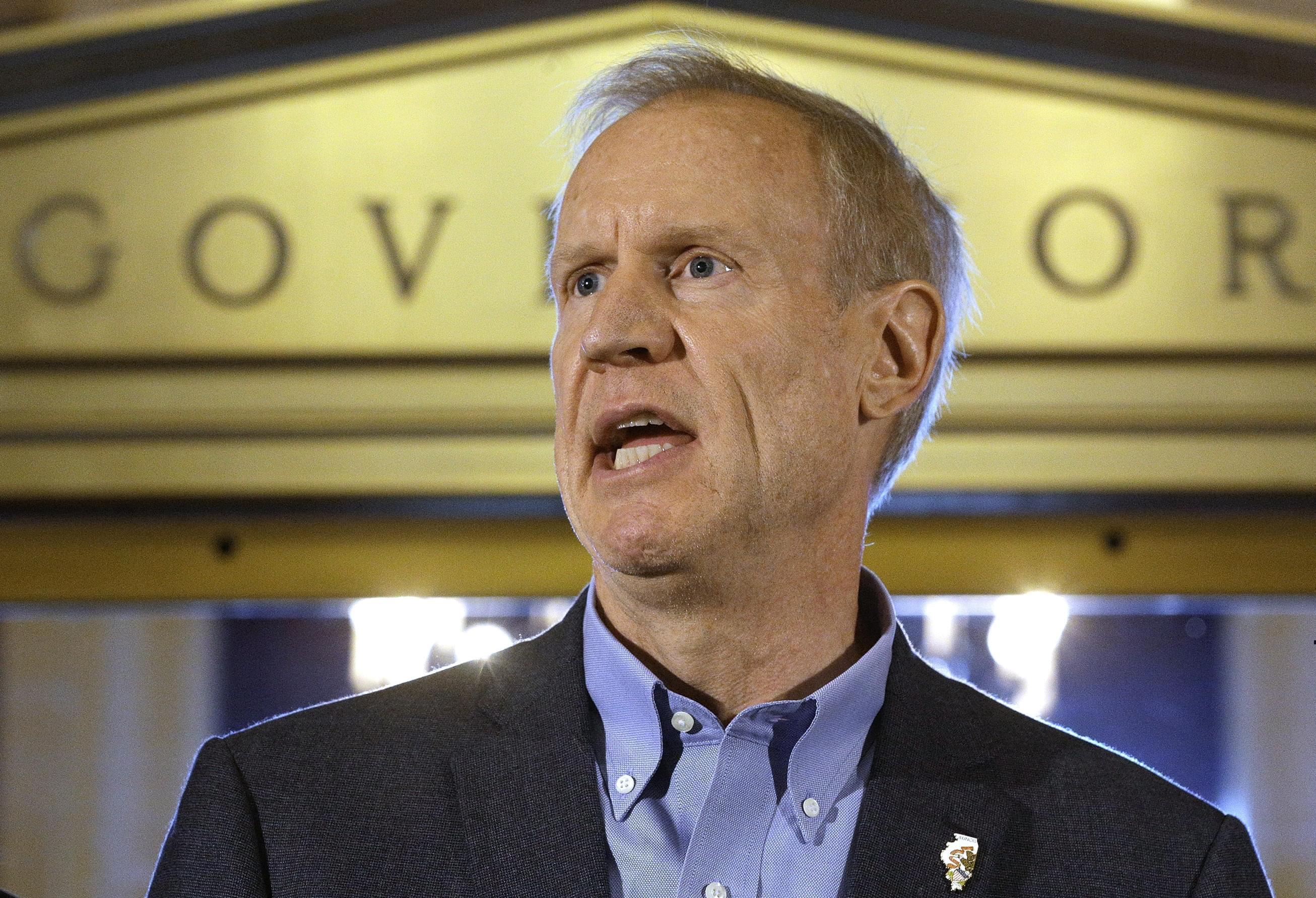 In this Thursday, June 30, 2016 photo, Illinois Gov. Bruce Rauner speaks to reporters in front of his office at the Illinois State Capitol in Springfield, Ill., after lawmakers passed a stop gap budget.