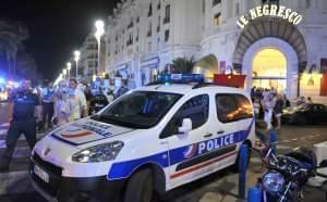 A Police car is parked near the scene of an attack after a truck drove on to the sidewalk and plowed through a crowd of revelers who'd gathered to watch the fireworks in the French resort city of Nice, southern France, Friday, July 15, 2016. A s