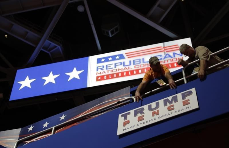 Workers place a sign as they prepare at Quicken Loans Arena in Cleveland for the Republican National Convention .