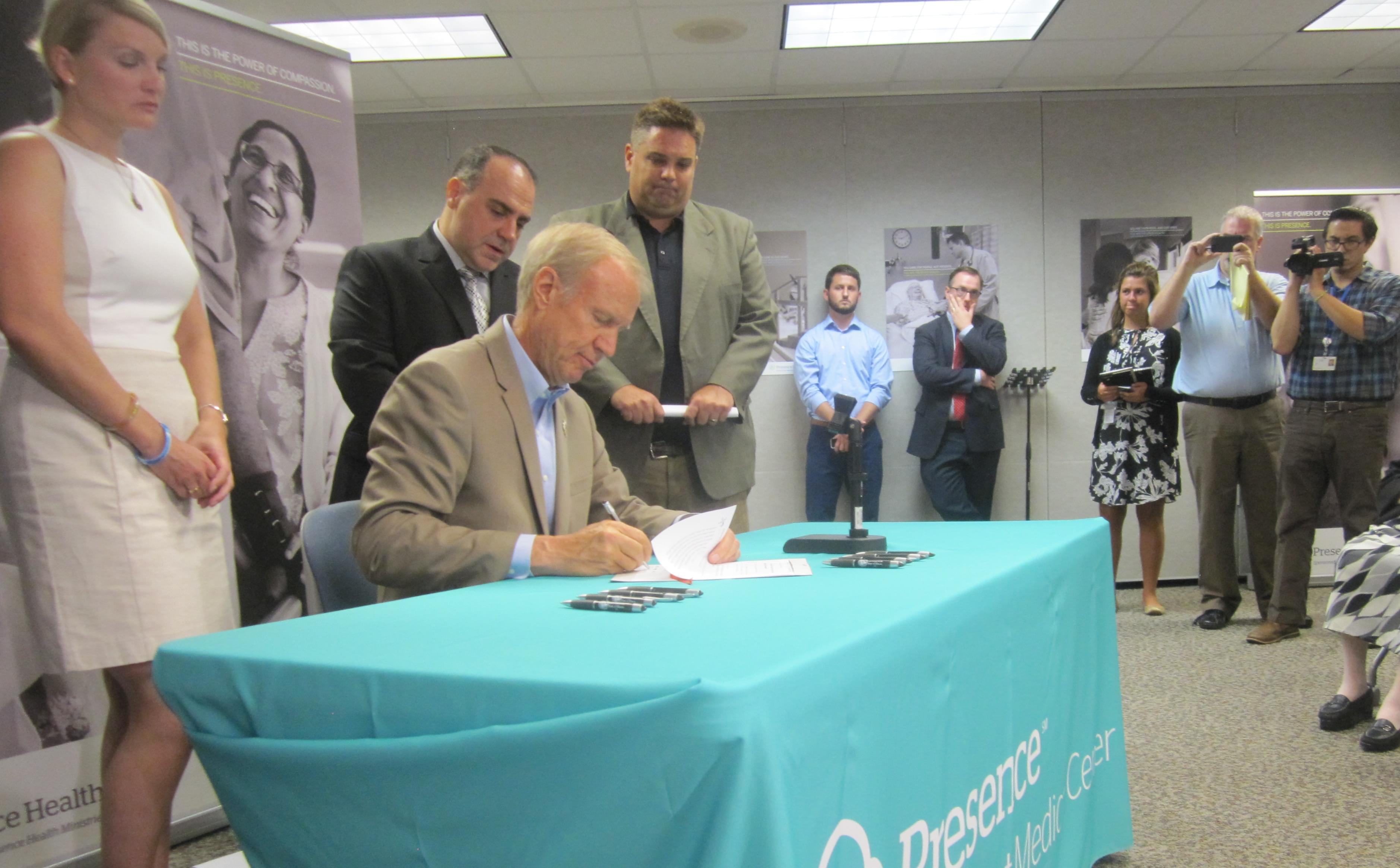Gov. Bruce Rauner signing legislation.