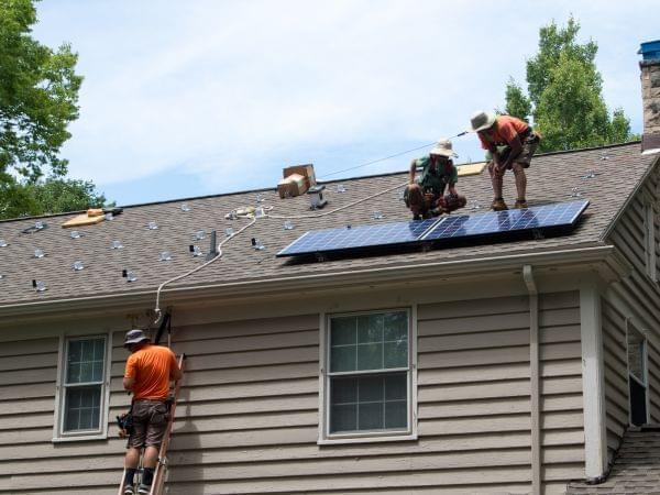 Two men on a roof placing solar panels. Another climbs toward them on a ladder.