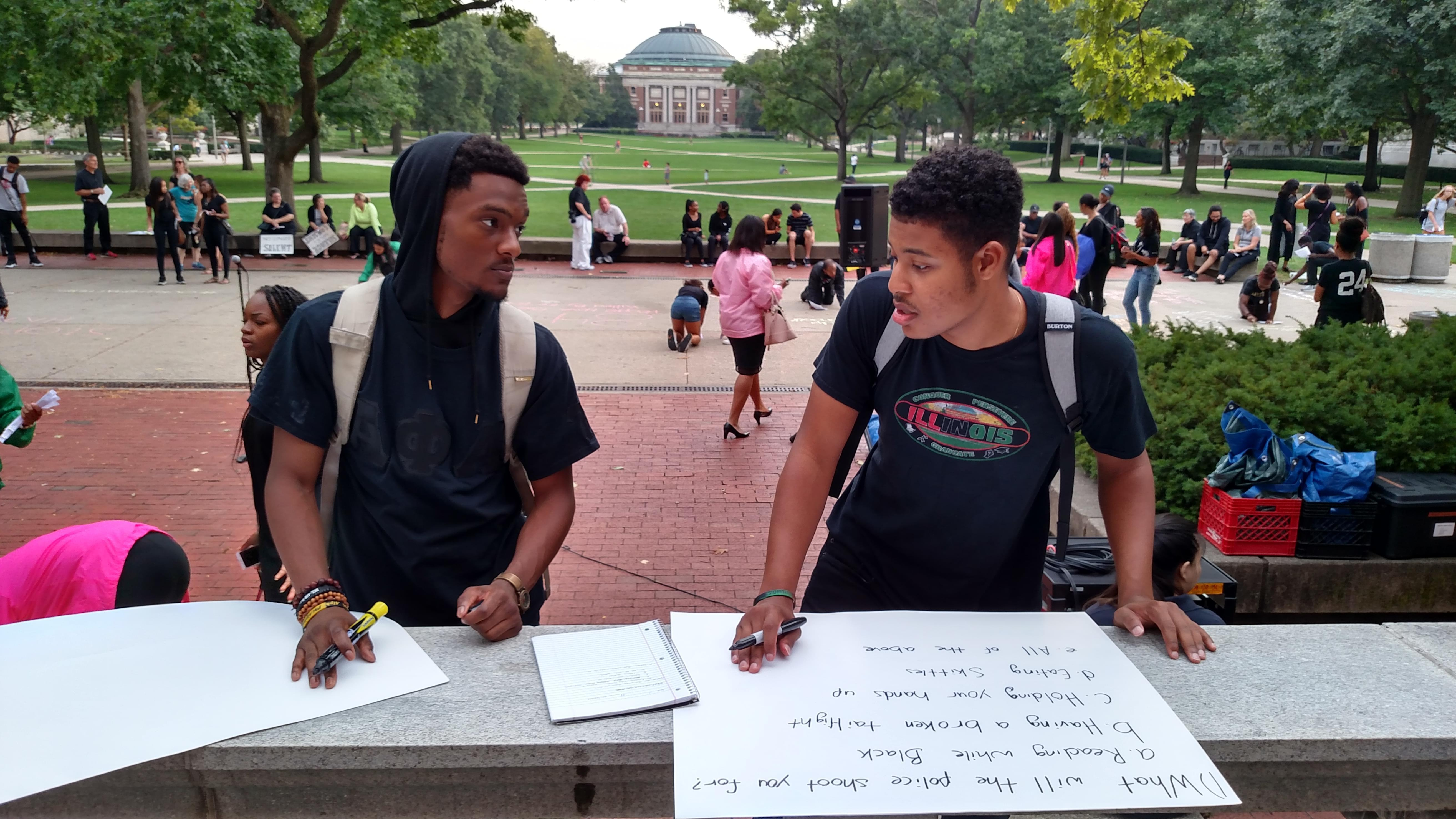 """Undergraduate students Immanuel Campbell and Marques Webster create signs during a """"Call To Action"""" event on the University of Illinois Main Quad on Sunday, September 25, 2016."""