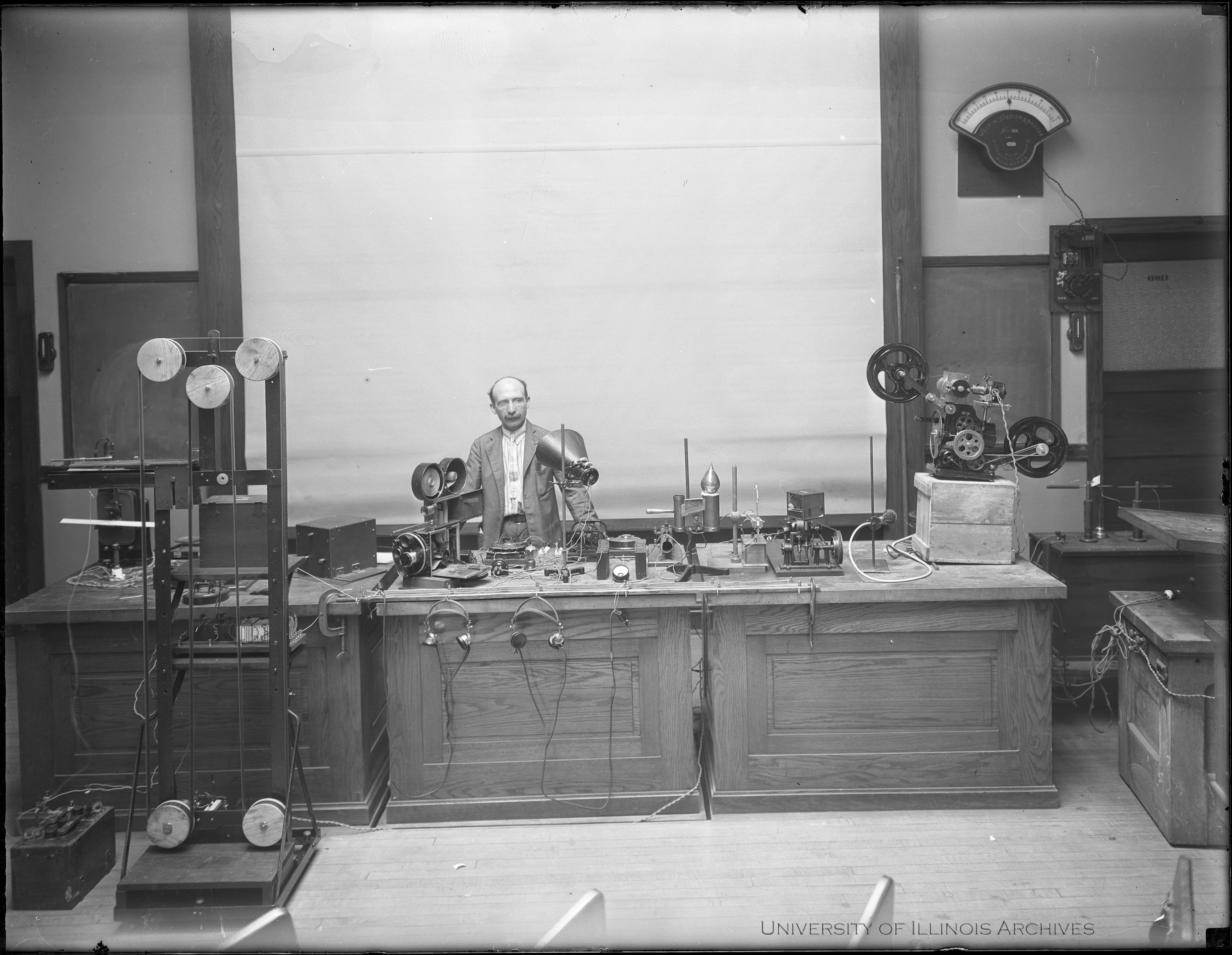 Joseph Tykociner, University of Illinois professor of electrical engineering, stands with all of the equipment used to create sound motions pictures in the world's first successful demonstration of sound on film. This demonstration was in the Ph
