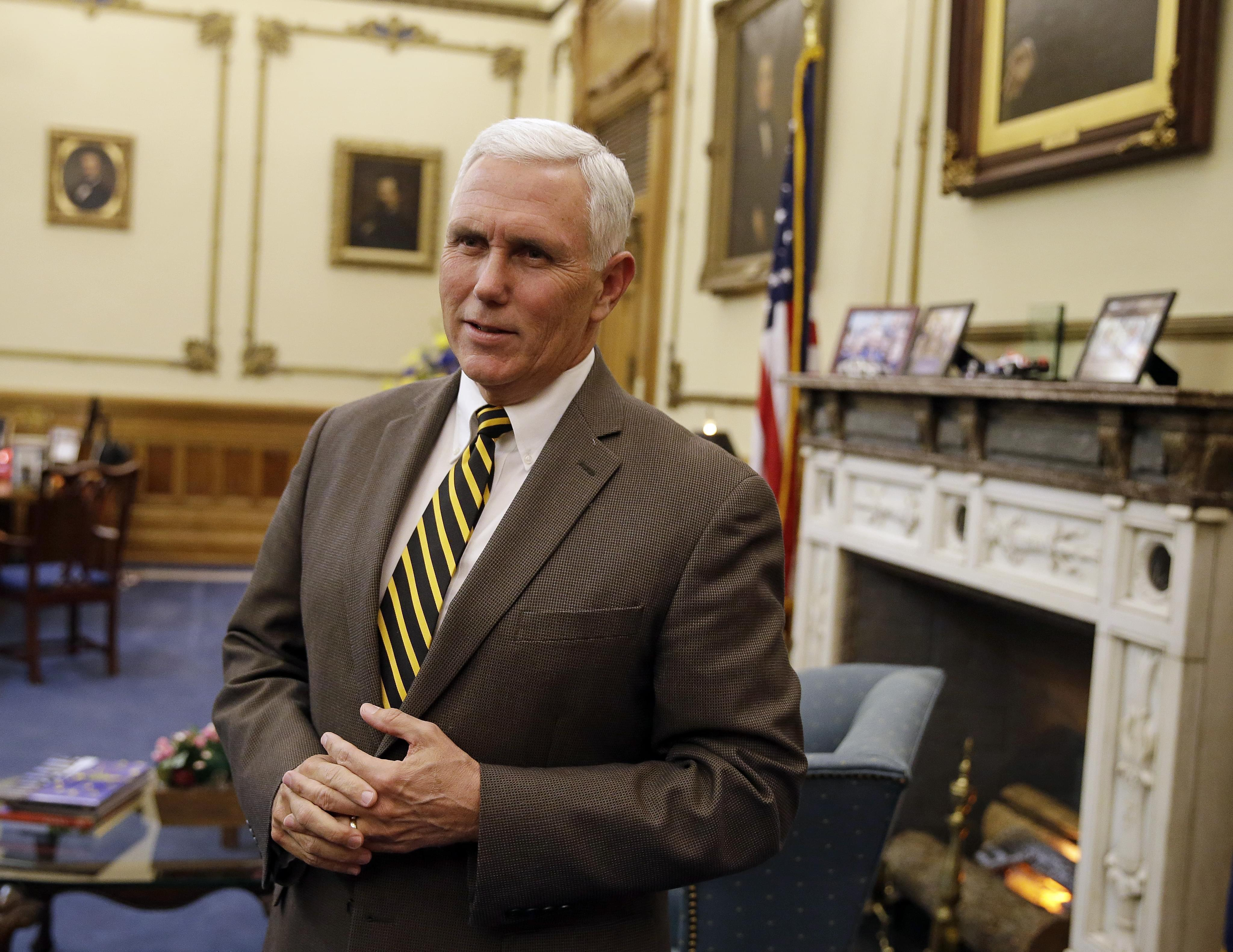 Indiana Gov. Mike Pence speaks after a meeting with Indianapolis Archbishop Joseph Tobin at the Statehouse Wednesday, Dec. 2, 2015, in Indianapolis, a day after the archdiocese said it has the means to resettle a Syrian refugee family bound for the s