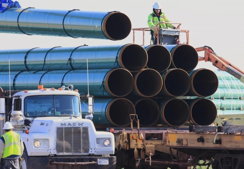 workers unload pipes for the proposed Dakota Access oil pipeline that would stretch from the Bakken oil fields in North Dakota to Illinois.