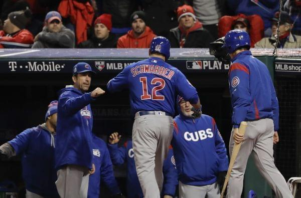 Chicago Cubs' Kyle Schwarber celebrates in the dugout after gets walked in during the fifth inning of Game 2 of the World Series against the Cleveland Indians Wednesday, Oct. 26, 2016, in Cleveland