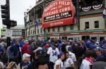 Fans wait in front of the Wrigley Field marquee as they arrive before Game 3 of the  World Series between the Chicago Cubs and the Cleveland Indians, Friday, Oct. 28, 2016, in Chicago.