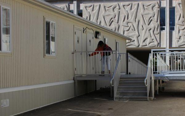 A student enters a portable classroom outside of Centennial High School.