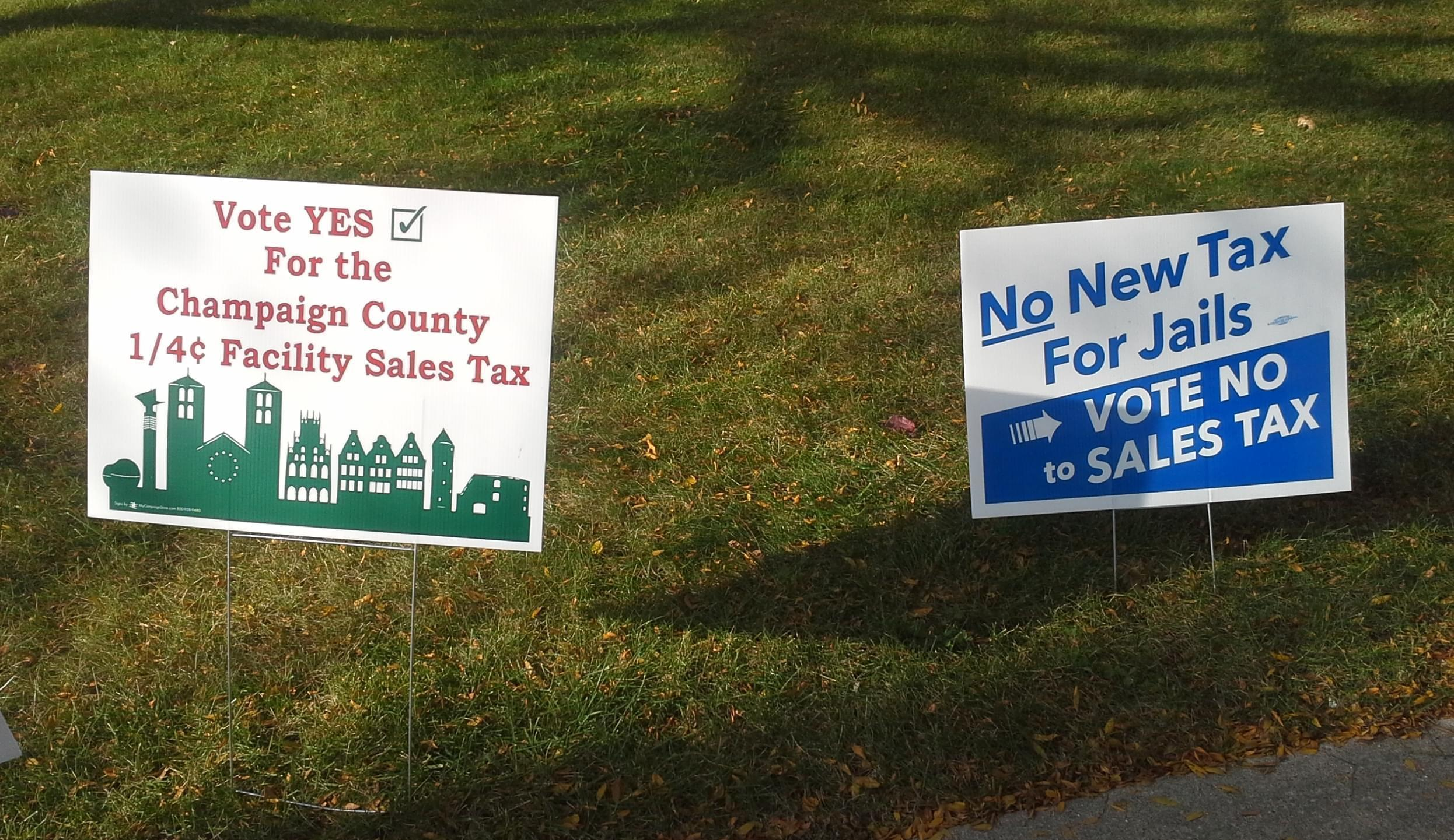 Two yard signs, one for and one against the Champaign County Facilities Sales Tax referendum.