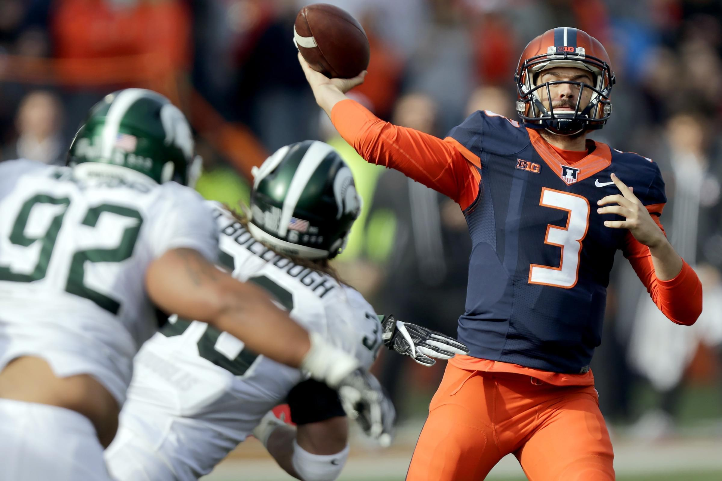 Illinois quarterback Jeff George Jr. passes against the defense of Michigan State linebacker Riley Bullough  and defensive tackle Kevin Williams  during the second half of an NCAA college football game at Memorial Stadium on Saturday.