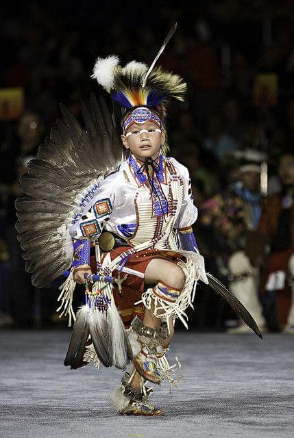 Elementary age Native American boy  in ceremonial dress dancing