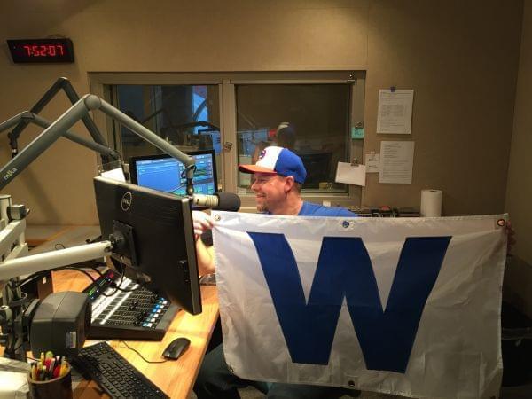 "A man holding a Cubs ""W"" flag."