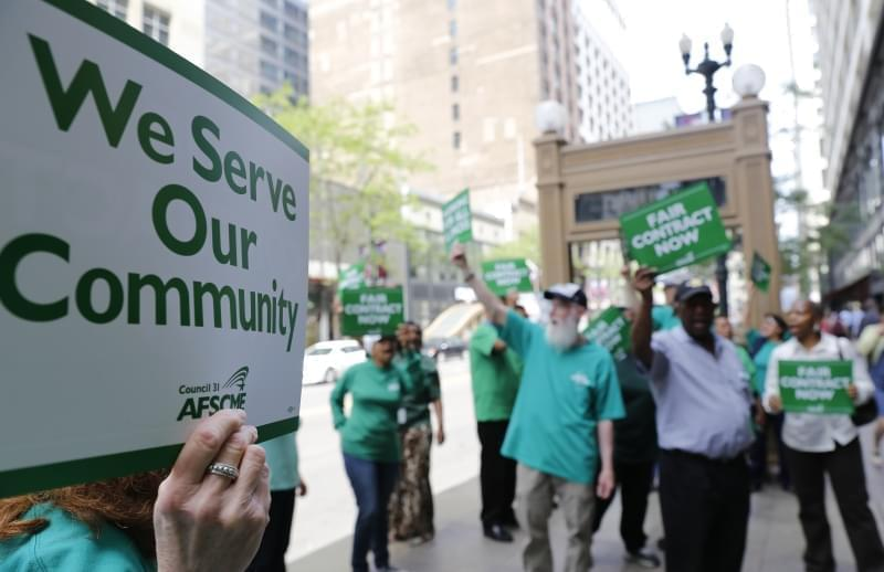 In this June 9, 2015 photo, members of the American Federation of State, County and Municipal Employees protest in Chicago.