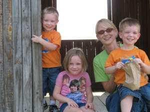 Mother, twin boys, and little girl smiling