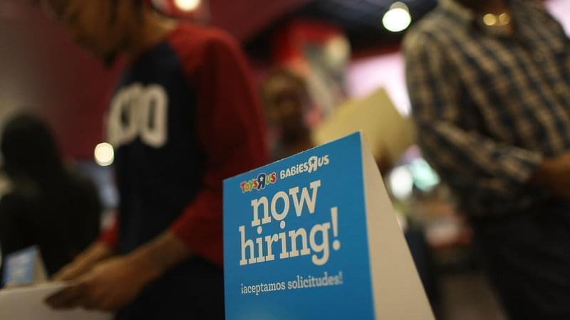 A now hiring sign at a job fair in Florida.
